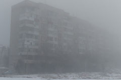 Mång--våning byggnad i dimman dimmig morgonvinter Royaltyfria Foton
