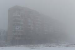 Mång--våning byggnad i dimman dimmig morgonvinter Arkivfoto