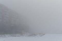 Mång--våning byggnad i dimman dimmig morgonvinter arkivfoton