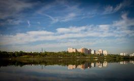 Mång--våning byggnader reflekteras i floden Fotografering för Bildbyråer