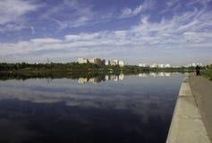 Mång--våning byggnader reflekteras i vattnet Royaltyfri Bild