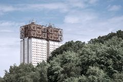 Mång--våning hus av den ovanliga designen mot himlen och skogen royaltyfria foton
