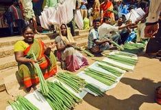 Många affärsmän av gröna grönsaker som väntar på kunder på bönder, marknadsför Royaltyfri Bild
