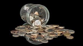 Många amerikanska mynt som hälls från en glass krus Royaltyfria Bilder