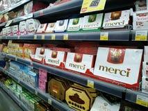 Många askar av olika chokladgodisar på hyllorna säljs i en stormarknad arkivbild