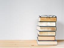 Många böcker för att studera och svarta exponeringsglas Arkivbild