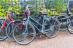 Många bicyces som parkeras i gatan, Holland stad Leiden Arkivbild