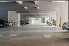 Många bilar i inre byggnad för parkeringsgarage Royaltyfri Bild