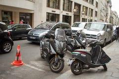 Många bilar och motorcyklar flyttar sig och parkerat i de gamla gatorna i mitten av Paris royaltyfri bild
