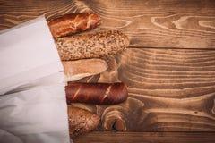 Många blandade bakade bröd och rullar på den lantliga trätabellen Royaltyfria Foton