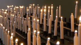 Många brännande stearinljus i kristen kyrka stock video