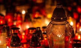 Många brännande stearinljus i kyrkogården på natten på tillfälleminnet av det avlidet souls arkivfoto