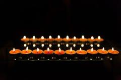 Många brännande stearinljus med grunt djup av fältet Fotografering för Bildbyråer