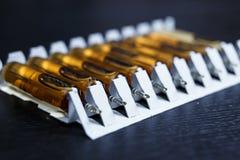 många bruna ampuller ställde in i farmaceutiskt den vita contaien för förpacka royaltyfria bilder