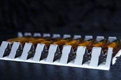 många bruna ampuller ställde in i farmaceutiskt den vita contaien för förpacka arkivbild
