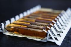 många bruna ampuller ställde in i farmaceutiskt den vita contaien för förpacka arkivbilder