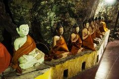 Många buddha och gud och ängel och enslingstaty i grotta på Wat Khao Orr arkivbild
