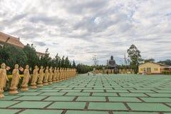 Många Buddhastatyer i perspektiv på den buddistiska templet Royaltyfria Bilder