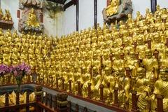 Många buddistiska gudstatyer i den forntida longhuatemplet veven för byggnadsporslinkonstruktion avslutade moderna nya kontorssha Royaltyfri Fotografi