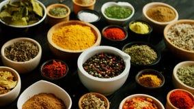 Många bunkar med olika kryddor arkivfoto