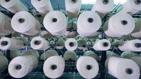 Många clews i rader roterar på en kugge som rullar ihop fiber arkivfilmer