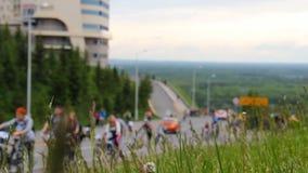 Många cyklister och fotgängare går uppåt- och neråt en kulle Spikelets av gräs som skakar från vind på framdel stock video
