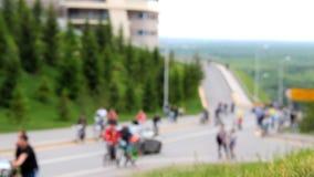 Många cyklister och fotgängare går vidare vägen Kulle som täckas med träd för grönt gräs och päls stock video