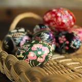Många dekorerade påskägg ligger i en korg, blå bakgrund Ukrainska p?sk?gg med prydnader och modeller royaltyfri foto