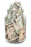 Många dollar i en glass krus Arkivbild