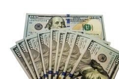 Många dollar isoleras på en vit bakgrund arkivfoto