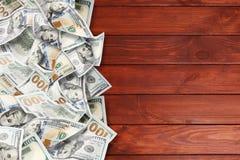 Många dollar på en träbakgrund arkivbild