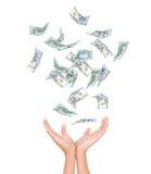 Många dollar som faller på kvinnas hand Arkivbild