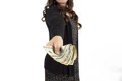 Många dollar som faller på kvinnas hand med pengar Royaltyfri Foto