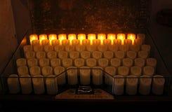 Många elektriska plast- votive stearinljus i en katolsk kyrka Arkivbilder