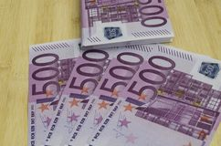 Många 500 euroräkningar på en trätabell Arkivfoto