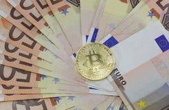 Många 50 eurosedlar och det guld- BitCoin myntet Royaltyfri Bild