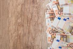 många 50 eurosedlar på träskrivbordet Arkivfoton