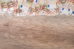 många 50 eurosedlar på träskrivbordet Arkivbild