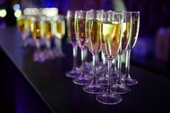 Många exponeringsglas av champagne på en tabell Royaltyfri Bild