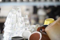 Många exponeringsglas och kaffekoppar som staplas på hylla i coffee shop royaltyfria foton