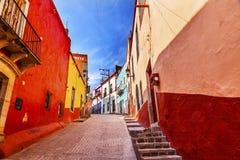 Många färgade den smala gatan Guanajuato Mexico för röda gula hus arkivfoton