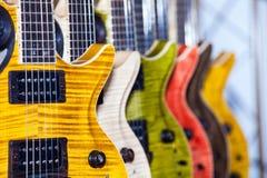 Många färgrika gitarrer i musikal shoppar arkivfoton