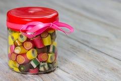Många färgrika godisar i stängd glass krus med det rosa bandet på det Arkivfoto
