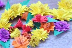 Många färgrika pappers- blommor på en bakgrund med en slät surfac Arkivfoto