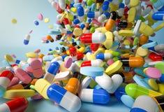Många färgrika preventivpillerar och kapslar som faller på vit bakgrund Royaltyfria Bilder