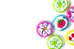Många färgrika runda fruktgodisar med fruktbilder på vit bakgrund med kopieringsutrymme royaltyfri foto