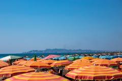 Många färgrika solparaplyer och slags solskydd på en strand i Albanien med horisonten och stad i bakgrunden fotografering för bildbyråer