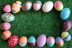 Många färgrikt utsmyckat easter ägg som målas på grön gräsmattabakgrund, festligt feriehändelsebegrepp arkivfoto