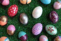 Många färgrikt utsmyckat easter ägg som målas på grön gräsmattabakgrund, festligt feriehändelsebegrepp fotografering för bildbyråer