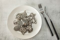 Många fejkar brusanden diamantsmycken på en platta med en kniv och en gaffel arkivbild